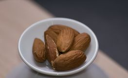 Almonds on a white serving plate, close up. Almonds on a white serving plate, side view Royalty Free Stock Photos