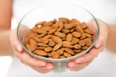 Almonds - woman showing raw almond bowl close up Stock Photos