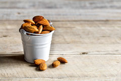Almonds on wooden background in a bucket . healthy, tasty. Food Royalty Free Stock Image