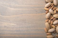 Almonds on wooden background. Raw almonds, with skin and rind on wooden background stock photography