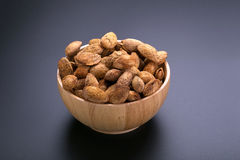 Almonds in wooden bowl on a black background Stock Photo