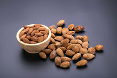 Almonds in wooden bowl on a black background Royalty Free Stock Image