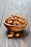 Almonds in a wooden bowl. Closeup on wooden background Stock Photography