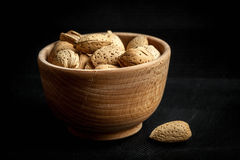 Almonds in a wooden bowl. Almonds in a wooden bowl on a dark background. Dark light Stock Images