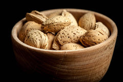 Almonds in a wooden bowl. Almonds in a wooden bowl on a dark background. Dark light Stock Photography