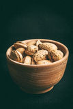 Almonds in a wooden bowl. Almonds in a wooden bowl on a dark background. Dark light. Instagram style filtred image Royalty Free Stock Photo