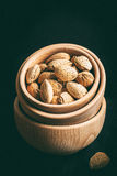 Almonds in a wooden bowl. Almonds in a wooden bowl on a dark background. Dark light. Instagram style filtred image Stock Images
