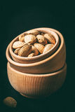 Almonds in a wooden bowl. Almonds in a wooden bowl on a dark background. Dark light. Instagram style filtred image Royalty Free Stock Image