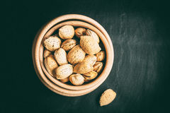 Almonds in a wooden bowl. Almonds in a wooden bowl on a dark background. Dark light. Instagram style filtred image Royalty Free Stock Photos