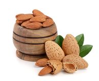 Almonds in a wooden bowl with leaves isolated on white background.  Stock Photo
