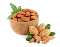 Almonds in a wooden bowl with leaves isolated on white background.  Royalty Free Stock Images