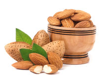 Almonds in a wooden bowl with leaves isolated on white background.  Stock Images