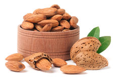 Almonds in a wooden bowl with leaves isolated on white background.  Stock Photos
