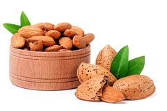 Almonds in a wooden bowl with leaves isolated on white background.  Royalty Free Stock Photography