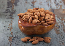 Almonds in a wooden bowl. On the old wooden blue table Royalty Free Stock Photo