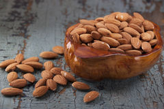 Almonds in a wooden bowl. On the old wooden blue table Stock Photos