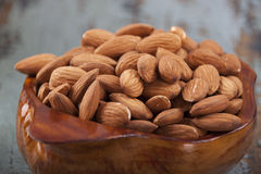 Almonds in a wooden bowl. On the old wooden blue table Royalty Free Stock Images