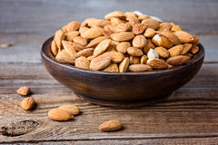 Almonds on a wooden bowl. Royalty Free Stock Photos