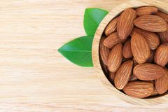 Almonds in wooden bowl on wood table Stock Image