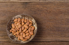 Almonds in wooden bowl on wooden board Stock Images