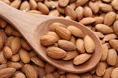 Almonds on a wooden spoon. On almonds background. Close-up Royalty Free Stock Photography