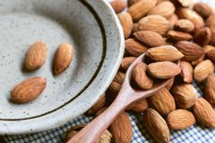 Almonds in the wooden spoon with a green ceramic dish on the blu stock image