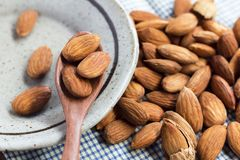Almonds in the wooden spoon with a green ceramic dish on the blu stock photos