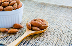 Almonds in wooden spoon on hemp Royalty Free Stock Image