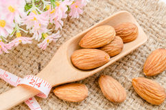 Almonds in wooden spoon with measure tape Royalty Free Stock Images