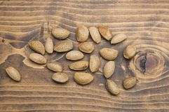 Almonds on wooden table. Raw almonds, with skin and rind on wooden background stock images