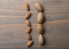 Almonds on wooden table. Raw almonds, with skin and rind on wooden background stock photo