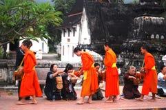 Almsgiving om kleverige rijst in Luang Prabang CIT te zetten Stock Foto's