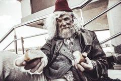 Almsman caucasiano que senta e que come o bolo que ele que encontra na rua fotos de stock royalty free