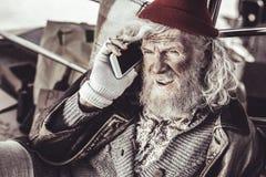 Almsman idoso que encontra o telefone novo e que decide chamar a alguém imagens de stock royalty free