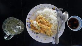Almuerzo con arroz y tortilla cocinada, salsa de chile y t? helado fotos de archivo