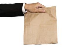 Almuerzo de la bolsa de papel marrón de la tenencia de la mano del hombre de negocios (distribución, dando), aislado en el fondo  Fotos de archivo libres de regalías