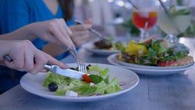 Almuerzo de la dieta sana, primer de las manos que come la ensalada útil vegetal de la placa durante tiempo de la comida en resta almacen de metraje de vídeo