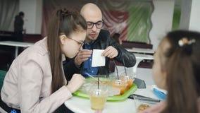 Almuerzo de la familia en el café El padre y dos hijas que comen juntos en tallarines de un café y beben exprimido recientement metrajes
