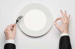 Almuerzo de negocios y tema sano de la comida: la mano del hombre en un traje negro que sostiene una placa vacía blanca y el fing fotografía de archivo