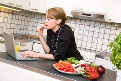 Almuerzo en cocina con la computadora portátil Imagen de archivo