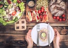 Almuerzo en la tabla con diversa comida, las manos de las mujeres con una placa imagenes de archivo
