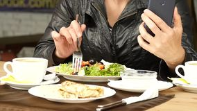 Almuerzo en un café al aire libre empresaria que come el correo electrónico de la ensalada y de los controles en su teléfono Cáma metrajes