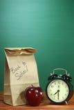 Almuerzo escolar, Apple y reloj en el escritorio en la escuela Fotos de archivo