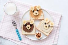 Almuerzo escolar o desayuno para los niños Tostada del plátano de la mantequilla de cacahuete con la cara animal imagen de archivo libre de regalías