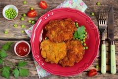 Almuerzo: las chuletas de cerdo con pan forman una costra, los guisantes verdes y los tomates Foto de archivo libre de regalías