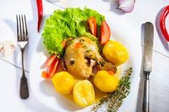 Almuerzo o cena caluroso: la placa de ckicken la pierna y las patatas con lechuga de hoja verde, tomates rojos en la superficie b Fotografía de archivo
