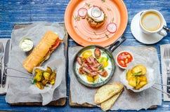 Almuerzo para dos: sartén con los huevos y tocino, patatas, bocadillo, salsa y café, cubiertos, en un fondo azul del dril de algo imagen de archivo libre de regalías