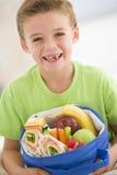 Almuerzo pila de discos explotación agrícola joven del muchacho en sala de estar Foto de archivo libre de regalías