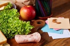Almuerzo sabroso con lechuga y verduras verdes en fuentes del envase y de escuela, en el escritorio de madera, foco selectivo Imagenes de archivo
