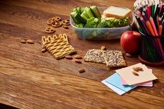 Almuerzo sabroso con lechuga y verduras verdes en fuentes del envase y de escuela, en el escritorio de madera, foco selectivo Imágenes de archivo libres de regalías
